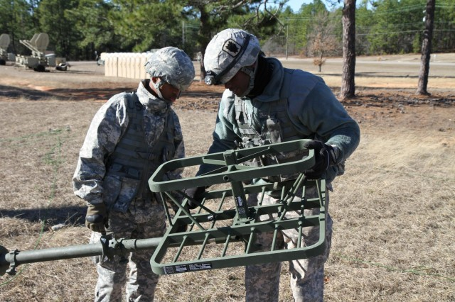 Sgt. Leroy Smith Jr., a multichannel systems operator assigned to Alpha Company, 67th Expeditionary Signal Battalion, instructs Pvt. Dommonic T. Thigpen, a cable systems installer, how to set up an antenna at a training site on Fort Gordon, Ga. The 35th Signal Brigade held a field training exercise at Fort Gordon Ga., Joint Base Lewis-McChord, Wash., and Fort Bragg, N.C., to validate and train on communication systems. Capt. Devon O. Thomas / 35th Signal Brigade Public Affairs