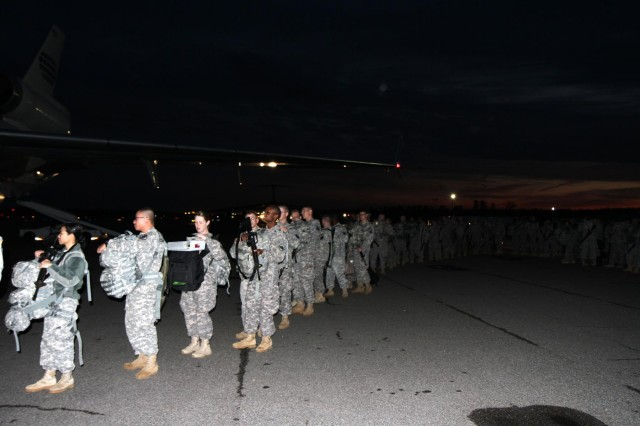 Soldiers assigned to the 67th Signal Battalion (Expeditionary) line-up to board the plane and deploy to the Middle East. (Sgt. Dianne M. Carter / 35th Signal Brigade)
