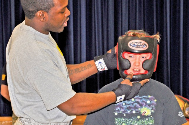 Spc. Rubin Stackhouse, a members of the U.S. Army Garrison Wiesbaden Boxing Team, adjusts a helmet on Aukamm Elementary School fifth-grader David Maxwell while talking about boxing safety gear.