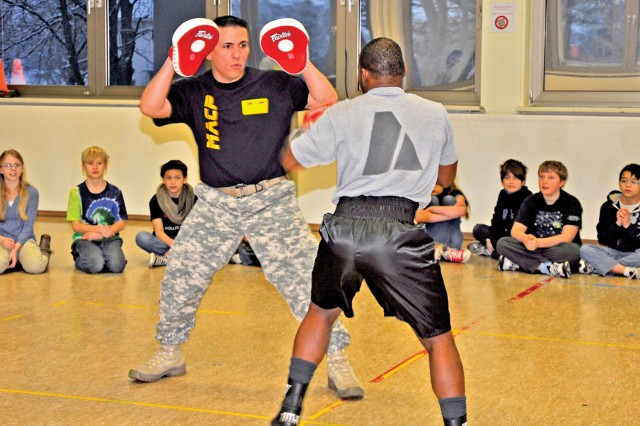 Sgt. 1st Class Adam Martinez, coach of the U.S. Army Garrison Wiesbaden Boxing Team, practices with team member Spc. Rubin Stackhouse during a talk about boxing and bullying at the Aukamm Elementary School Feb. 6.