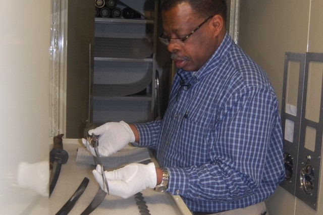 William Johnson, curator of collection, Rock Island Arsenal Museum, examines a sword that's a part of the museum's vast weapons collection.