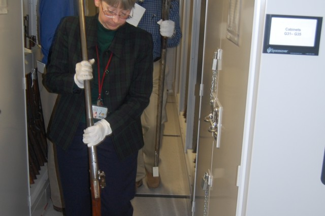 Kris Leinicke, director, Rock Island Arsenal Museum, and William Johnson, curator of collection, Rock Island Arsenal Museum, carefully walk with two valuable rifles from the museum's vault.