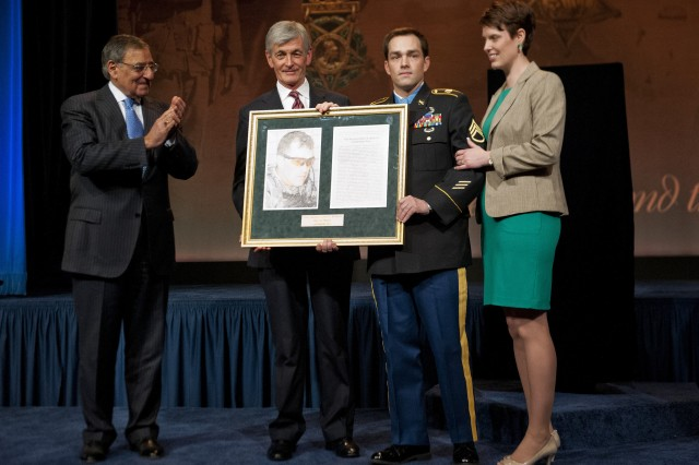 Secretary of Defense Leon E. Panetta and Secretary of the Army John M. McHugh presented former Staff Sgt. Clinton Romesha, Medal of Honor recipient, and his wife Tammy, with a frame containing both his picture and a copy of his Medal of Honor citation, Feb. 12, 2013. The noncommissioned officer earned the Medal of Honor for actions in Afghanistan, Oct. 3, 2009.  The president of the United States presented him with the medal during a ceremony, Feb. 11, at the White House.
