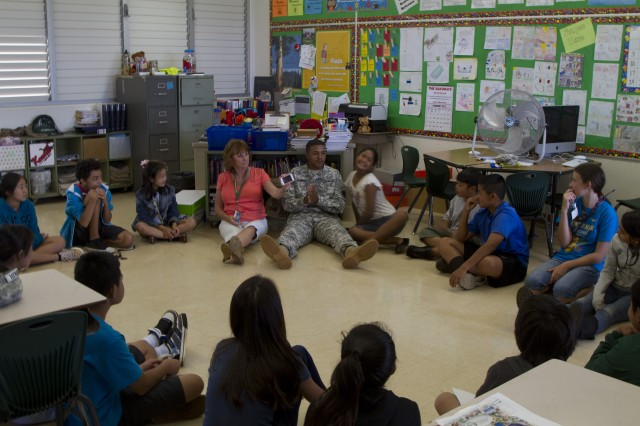 Spc. Quinten Booker, an information technician for the 8th Special Troops Battalion, 8th Theater Sustainment Command, sits with students of Gustav H. Webling Elementary School during his very last visit to the school.