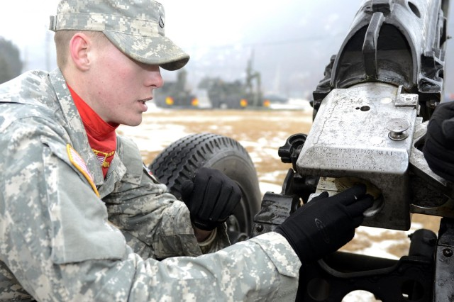 "Pfc. Christian Neuhring, a Phoenix native and a field artilleryman with the 1st Battalion, 15th Field Artillery Regiment, 1st Armored Brigade Combat Team, inserts a charge into the 75mm M1A1 Pack Howitzer for the salute battery during a 2nd Infantry Division ceremony. Neuhring's howitzer is named ""1st Lt. Lee Hartell,"" after a 2nd Infantry Division Korean War Medal of Honor recipient. (U.S. Army photo by Staff Sgt. Kyle Richardson, 1ABCT PAO)"