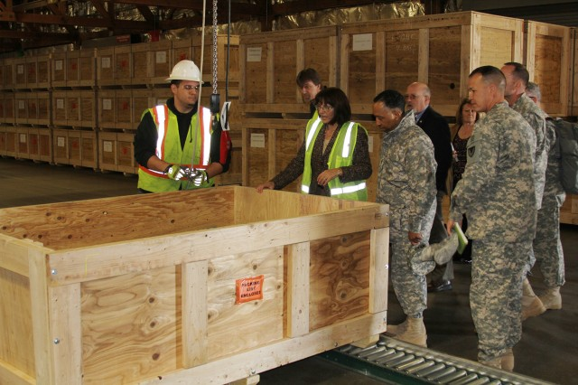 Susan Getty, director of Containerization and Assembly, explains to Gen. Dennis L. Via, commanding general of Army Materiel Command, the process once the add-on armor kits are complete and ready for packaging and storage.