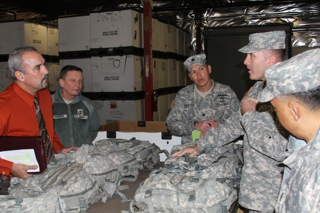 Command Sgt. Maj. Ronald Riling, Army Materiel Command senior enlisted adviser (second from right), discuss the type of clothing that is being returned from Soldiers in the field with John Dingman (far left), Maj. Gen. Michael Terry, Lt. Col. Christopher Dexter, and Gen. Dennis L. Via, commanding general of Army Materiel Command (far right).
