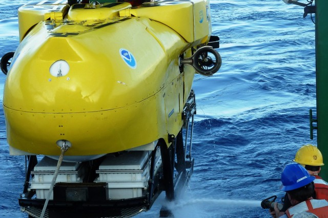 Crew members wash off the Pisces submersible before docking it on the research vessel off the coast of Hawaii.