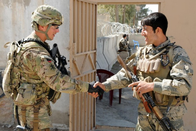A U.S. Army Soldier and Afghan Border Policeman exchange greetings after being assigned to the same area to provide security at the Spin Boldak, Afghanistan, district center for a district leaders' shura. The meeting was the first time that government, military and civilian leaders have come together to solve problems in the district.