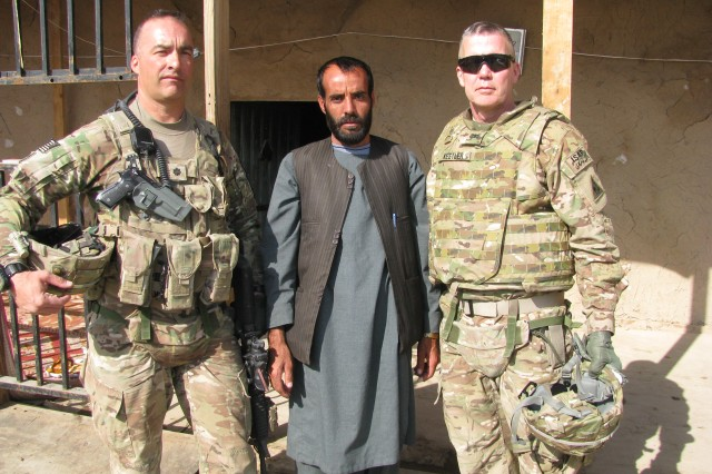 ARAF KALA, AFGHANISTAN--United States Army Reserve Soldier Col. Frank Kestler, of Shelter Island, N.Y. (right), New York Army National Guard Soldier Lt. Col. Russell Clark (left) and an Afghan National Police chief pose for a photo in Dand District, Afghanistan last autumn. Accompanied by Clark, his troops and the chief's police officers, Kestler journeyed to the Afghanistan field near Arif Kala where his  stepson, 1st Lt. Joseph Theinert, was killed in combat in June, 2010. At the site, Kestler prayed with the other Soldiers, gathered some earth and blessed the ground with holy water given to him by Chrys Kestler, Joe's mother. Clark is from Angola, N.Y.