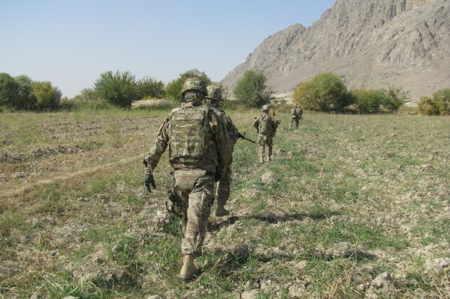 ARIF KALA, AFGHANISTAN--Accompanied by American troops and Afghan National Police, United States Army Reserve Soldier Col. Frank Kestler, of Shelter Island, N.Y. (foreground) walks to the Afghanistan field near Arif Kala where his  stepson, 1st Lt. Joseph Theinert, was killed in combat in June, 2010. Kestler, the troops and police officers conducted the patrol last autumn. At the site, Kestler prayed with the other Soldiers, gathered some earth and blessed the ground with holy water given to him by Chrys Kestler, Joe's mother.