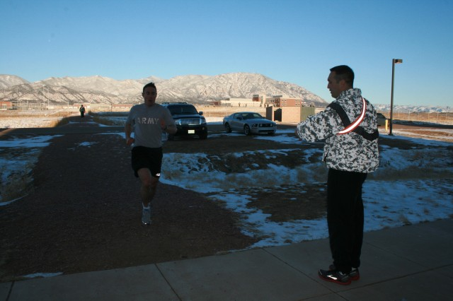 First Lt. Ken Rowe, 2nd Battalion, 12th Infantry Regiment, 4th Brigade Combat Team, 4th Infantry Division, completes his final 500-meter sprint, as Maj. Mark Ivezaj calls out the time, at Fort Carson, Colo.
