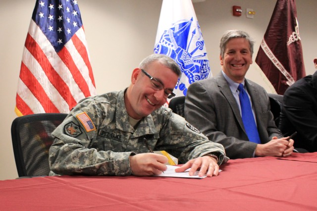 U.S. Army Medical Materiel Agency commander (left) Col. Alejandro Lopez-Duke, a subcommand of U.S. Army Medical Research and Materiel Command, signs a Cooperative Research and Development Agreement, Feb. 8, 2013, with the NeuroHabilitation Corporation, founded by celebrity Montel Williams and his colleagues, including the University of Wisconsin scientists. This agreement allows the Army to further evaluate the PoNS  device and its potential application as a treatment therapy for traumatic brain injury. This is USAMMA's first Cooperative Research and Development Agreement. Phil Deschamps, CEO of NeuroHabilitation Corporation, is also pictured (right).