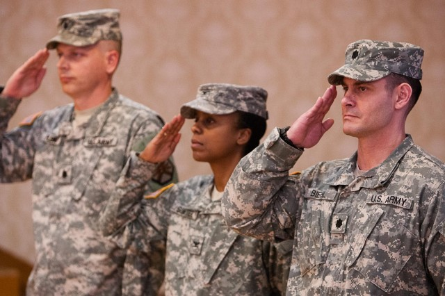 (From the left) Outgoing Headquarters Command Battalion Commander Lt. Col. Eric Fleming, Joint Base Myer-Henderson Hall Commander Col. Fern O. Sumpter and incoming Headquarters Command Battalion Commander Lt. Col. Mark Biehl render honors to the flag during a change of command ceremony in the community center Feb. 12.