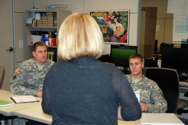 Two 470th Military Intelligence Brigade Soldiers learn Spanish from a contracted instructor through the brigade's Command Language Program. (U.S. Army photo by Gregory Ripps)