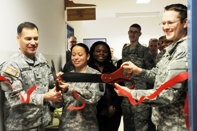 Col. Lee Rudacille, Joint Multinational Training Command commander, and Staff Sgt. Yasmina Gomez, from the 574th Quartermaster Supply Company, help Capt. Blaise Bess, 7th Army Joint Multinational Training Command Tax Officer in Charge, officially open the Bavarian Tax Centers in Grafenwoehr, Jan. 28.