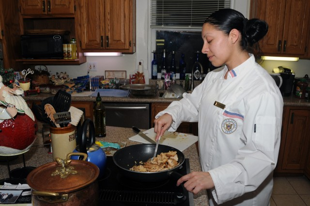 Sgt. 1st Class Sophia Bulham prepares food for a First Army Headquarters holiday open house at Lt. Gen. Mick Bednarek's home Dec. 15.