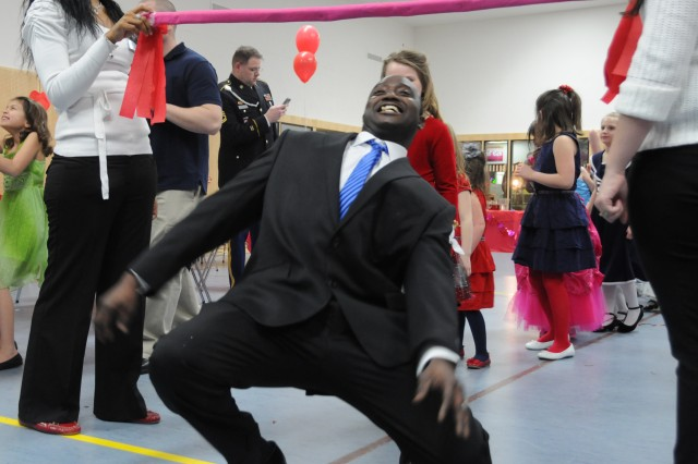 Sgt. Remond Joyner, Headquarters and Headquarters Company, 172nd Infantry Brigade, gets low during the limbo contest at the Daddy Daughter Dance, Feb. 13, 2013, in Eschenbach, Germany.