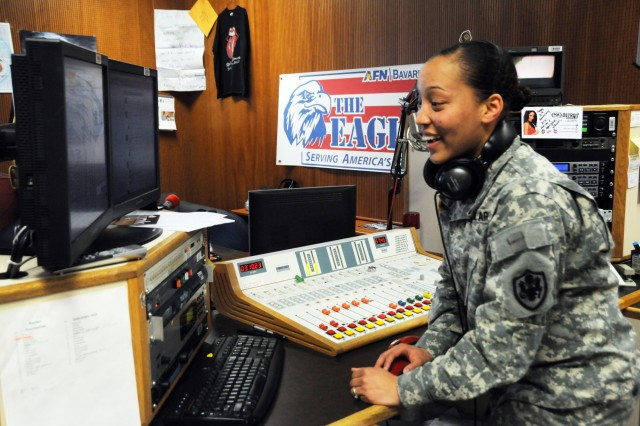 "Spc. Monique Moore, AFN Bavaria, rearranges her playlist in between songs during her afternoon radio show, Feb. 14. Moore, who has been on the radio since November, says of AFN: ""It's a great station. I'm looking forward to learning from everyone here."""