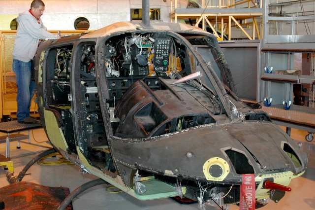 A Corpus Christi Army Depot aircraft production artisan repairs an aft fuselage section of an OH-58D Kiowa Warrior crash battle damaged helicopter.
