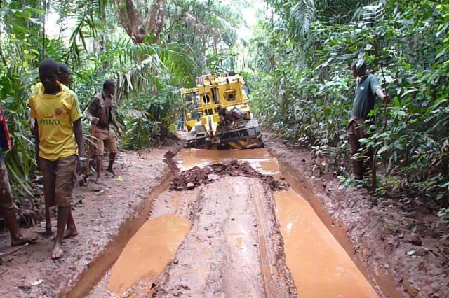 Workers slog equipment through a jungle to a LOGCAP-supported site in Africa. LOGCAP supports four sites on the continent.