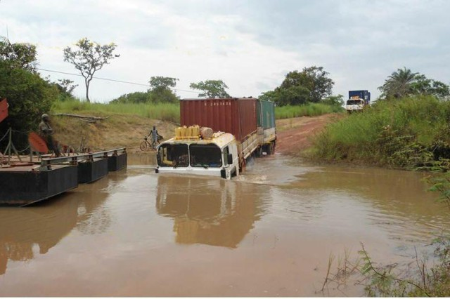 A truck and trailer laden with LOGCAP supplies cross a river en route to a LOGCAP-supported site in Africa. LOGCAP supports four sites on the continent.