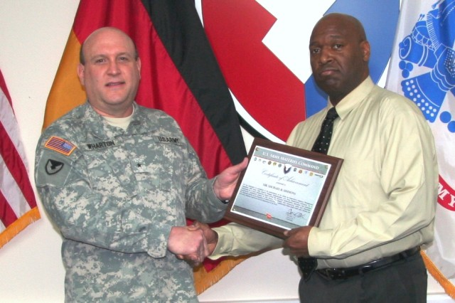 Brig. Gen. John F. Wharton, commanding general, Army Sustainment Command, presents Michael Simmons, logistics management specialist, Support Operations, 405th Army Field Support Brigade, Kaiserslautern, Germany, with the 2011 Louis Dellamonica Award Feb. 7. Simmons has the honor of being the only ASC employee to receive the award for 2011. (Photo by Steven Stanfill, 405th AFSB Public Affairs)