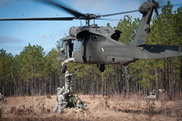 Artillerymen with the 82nd Airborne Division's 1st Brigade Combat Team prepare to hook up an M119A2 105mm howitzer to a UH60 Black Hawk helicopter during air assault training Feb. 8, 2013, at Fort Bragg, N.C.  The artillerymen are assigned to 3rd Battalion, 319th Airborne Field Artillery Regiment.  (U.S. Army photo by Sgt. Michael J. MacLeod)
