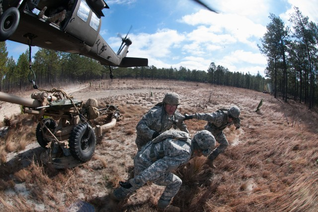 Artillerymen move out of the way after hooking up their howitzer to a UH60 Black Hawk helicopter during air assault training Feb. 8, 2013, Fort Bragg, N.C.  The helicopter is also carrying artillerymen who will fire the cannon once it is transported to another position.  (U.S. Army photo by Sgt. Michael J. MacLeod)