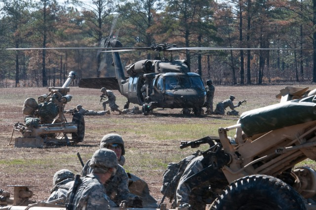 Paratroopers with the 82nd Airborne Division's 1st Brigade Combat Team exit a UH60 Black Hawk helicopter during air assault training Feb. 8, 2013, at Fort Bragg, N.C.  Their howitzer in the foreground was slung from the belly of the aircraft during flight.  (U.S. Army photo by Sgt. Michael J. MacLeod)