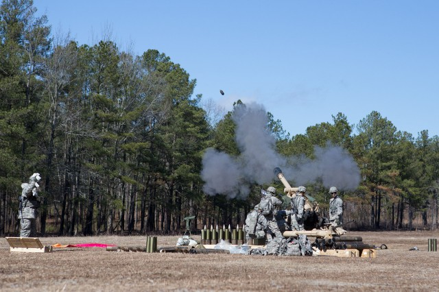 """Paratroopers with the 82nd Airborne Division's 1st Brigade Combat Team fire an M119A2 105mm howitzer during a """"gun raid"""" Feb. 8, 2013, at Fort Bragg, N.C.  The artillerymen emplaced their cannon via helicopter and quickly set it up to fire on """"enemy"""" positions.  (U.S. Army photo by Sgt. Michael J. MacLeod)"""