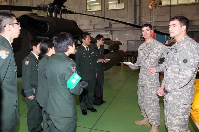 Chief Warrant Officer 2 Russell Reinemer, second from right, assigned to the 78th Aviation Battalion at Camp Zama, Japan, briefs students of the Japanese Ground Self-Defense Force's Advanced Officer English course from Camp Kodaira on the unit's during a visit to Camp Zama Jan. 23.