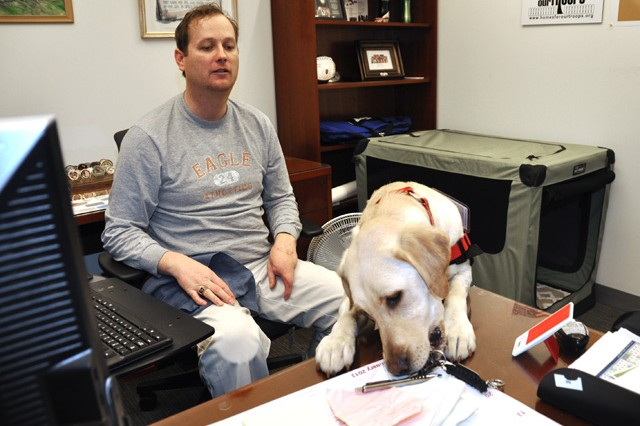 Equal Opportunity specialist and Wounded Warrior Kelly Keck watches as his service dog, Libby, retrieves keys from his desk at the ATEC Headquarters. Keck received the golden lab from Hero Dogs, a group that provides service dogs to veterans at no charge.