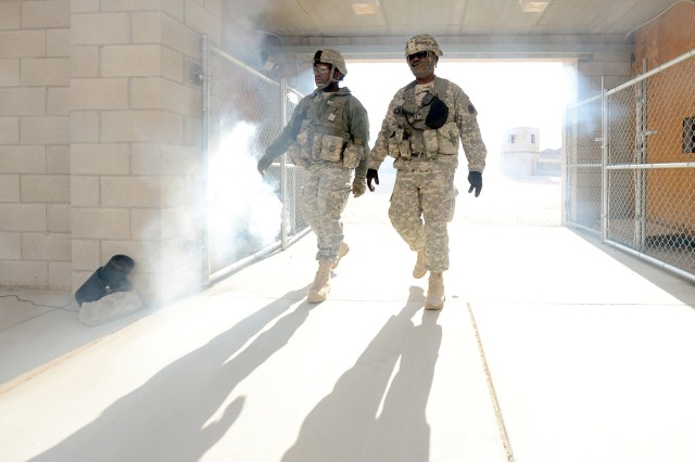 Pfc. Damien Davis (left) and Staff Sgt. James Bates, both of the Operations Group at the National Training Center in Fort Irwin, Calif., walk through a entryway obscured by smoke, Feb. 20, 2013. Their group is documenting the  2nd Brigade Combat Team, 1st Infantry Division, from Fort Riley, Kan., as they train at NTC as the first brigade to be aligned with U.S. Army Africa Command.