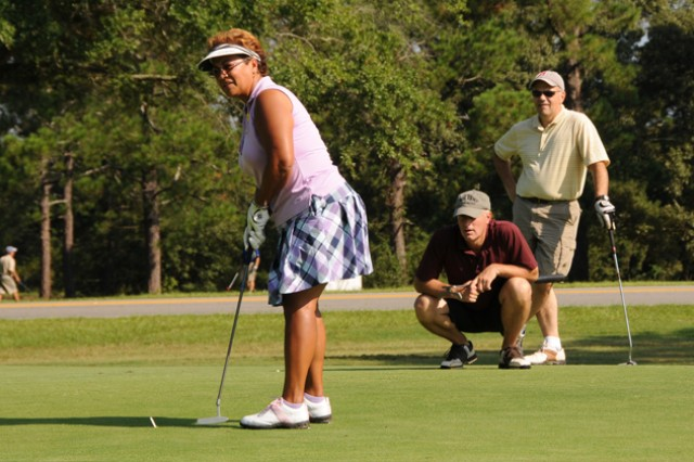 Eneicy Seitz, wife of Col. Steve Seitz, USAACE director of simulations, lines up a putt while her husband and friends watch during last year's Swing FORE Life Golf Tournament. The 2013 SWGC membership drive through the month of March looks to recruit new members while maintaining current members.