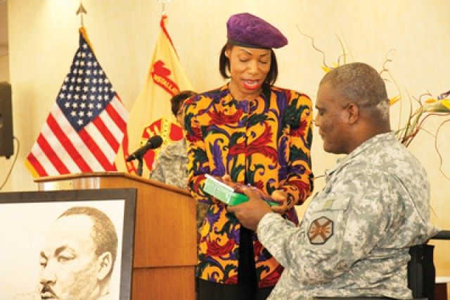 E.P.  McKnight, guest speaker at the cultural observance honoring at Martin Luther King Jr., Jan. 18 at the Officers' Club, presents Col. Gregory D. Gadson, Fort Belvoir garrison commander, with a copy of her most recent book.