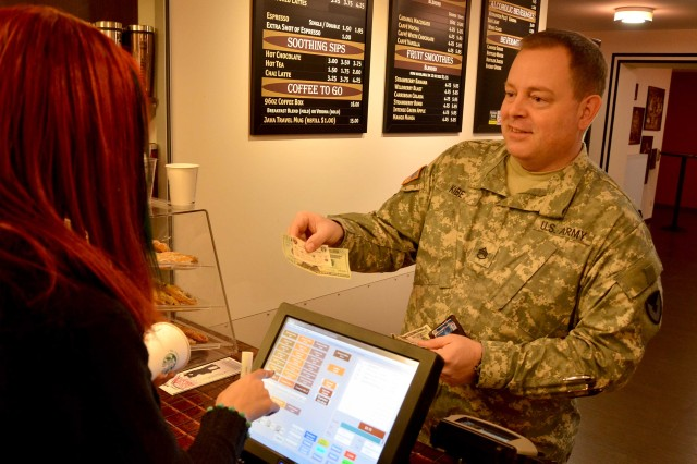 Staff Sgt. Joe Kibe, a noncommissioned officer with the 903rd Contingency Contracting Command, buys a coffee at the Java Cafe on Kleber Kaserne at U.S. Army Garrison Kaiserslautern. In the past year, he's paid off much of his debts.