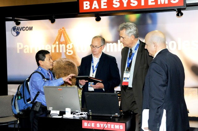 (From left) Paul Huang (Army Research Laboratory), Curtis Toone (BAE Systems), Kevin Flamm (Office of the Assistant Secretary of the Army for Acquisition, Logistics, and Technology) and Joe Forino (U.S. Army Research, Development and Engineering Command) discuss advanced manufacturing enterprise solutions that address obsolescence during product design at the Defense Manufacturing Conference in Orlando, Fla., Nov. 26, 2012.