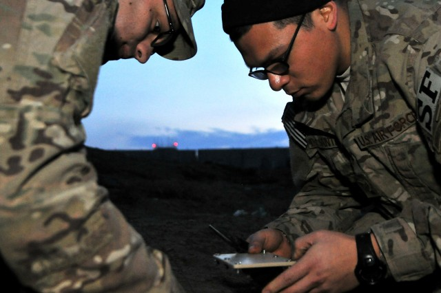 Tech. Sgt. John Dolbee (left) and Staff Sgt. Ben DeSantiago connect a power source to a ground sensor for an enemy movement and detection training scenario Feb. 14 at Bagram Airfield, Afghanistan. The team uses a series of search techniques from simple, eyes-on to ground sensors to track insurgent activity and provide site exploitation after an attack. Dolbee and DeSantiago are 755th Expeditionary Security Forces Squadron Reaper team trackers.