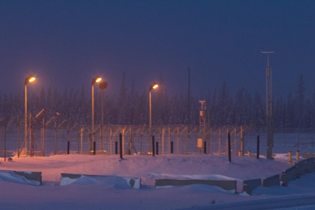 The moon sets over a fence line on the Missile Defense Complex at Fort Greely, Alaska.