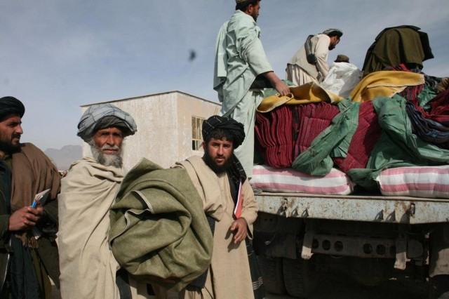 The Uruzgan Provincial Governor, Amir Mohammad Akhunzada and Director of Natural Disaster and Relief, Ismatullah Faiz distributes food and winterization items to the less fortunate within the Uruzgan province of Afghanistan, Feb. 2013.