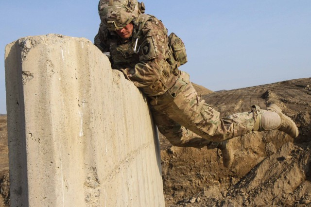 "KHOWST PROVINCE, Afghanistan "" Staff Sgt. Robert Dodge, a cavalry scout assigned to Troop B, 1st Squadron, 33rd Cavalry Regiment, 3rd Brigade Combat Team ""Rakkasans,"" 101st Airborne Division (Air Assault), hurls himself over a cement wall during the obstacle course portion of the brigade non-commissioned officer and Soldier of the quarter competition on Forward Operating Base Salerno, Afghanistan, Feb. 15, 2013. Competitors were timed on performing a five mile road march as well as complete five stations throughout the competition. (U.S. Army photo by Spc. Brian Smith-Dutton, Task Force 3/101 Public Affairs)"