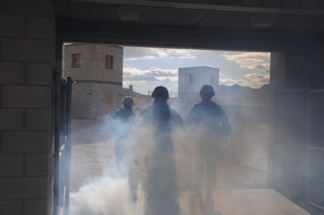 "Soldiers interact as smoke pours from a building in a mock town on the National Training Center at Fort Irwin, Calif. Soldiers of ""Dagger"" brigade are training for 14 days during the last two weeks of February 2013. The brigade will become regionally aligned to U.S. Africa Command by early May 2013."
