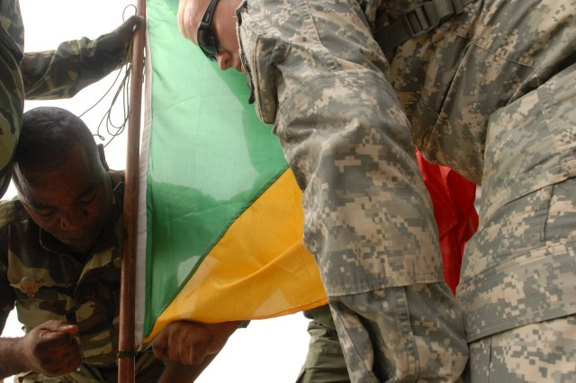 Spc. Alan Darger, a linguist from Sandy, Utah, with the 300th Military Intelligence Brigade, of the Utah Army National Guard, holds the Republic of Congo flag while Louika Parfait, a paratrooper from the Republic of Congo army ties to down for  the opening ceremony of exercise Central Accord 2013 Feb. 20. Cameroon and U.S. service members will partner throughout the 10-day exercise to hone aerial resupply and medical evacuation skills.