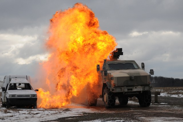 """A German Army """"Dingo"""" drives through a simulated roadside bomb blast during joint training with the 421st Multifunctional Medical Battalion at Baumholder Training Area Feb. 20. This training helps meet the U.S. Army Europe goal to strengthen interoperability of partner nations' land forces and set conditions that build coalitions for future overseas contingency operations."""