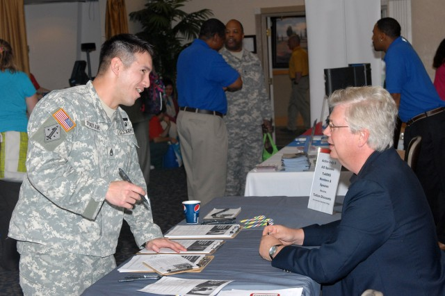 Staff Sgt. Thomas Statler, a patriot fire control enhanced operator/maintainer with the 4th Battalion, 5th Air and Missiles Defense Regiment, checks out education and job tables at Hood Howdy Feb. 7. Many Soldiers who are preparing to transition out of the Army visited the Hood Howdy job fair in Club Hood to gain informaiton on employment oppourtunities. (Photo by Sgt. William Begley, 11th PAD)