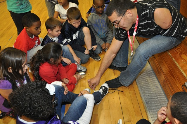 Retired Staff Sgt. Michael Kacer shows a group of children how to tie shoelaces with one hand during his visit to the APG South (Edgewood) youth center Feb. 15. A member of the U.S. Army Warrior Transition Command, stay-at-home dad and inspirational speaker, Kacer was a 2012 Army Warrior Games athlete and is in training for the 2013 games.