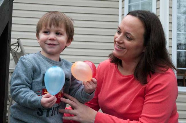 Ashley Broadway, spouse of Lt. Col. Heather Mack, 1st Theater Sustainment Command, has some balloon fun with their son Carson, 2 and a half. Broadway won Fort Bragg Military Spouse of the Year award. (Photo by Michelle Butzgy/Paraglide)