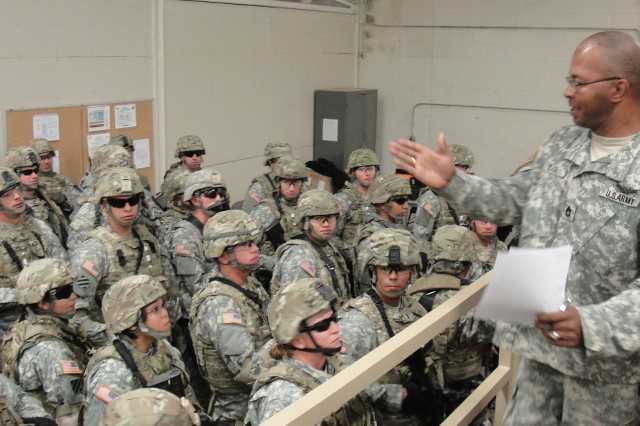 Sgt. 1st Class Kevin Earl, a trainer/mentor with 1st Battalion, 362nd Air Defense Artillery, Task Force Renegade, 5th Armored Brigade, Division West, instructs Soldiers of the 860th Military Police Company before they get in the mine-resistant ambush-protected vehicle egress trainer.