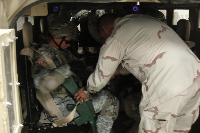 Domingo Perales, a civilian contractor with The Logistics Company, assists a Soldier with the 860th Military Police Company with proper wear of a passenger restraint system in the mine-resistant ambush-protected vehicle egress trainer.
